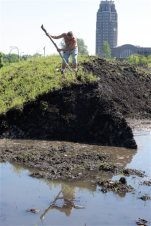 """Robert A. Raczka uses a stick on top of this dirt-covered snow """"glacier"""" that still hasn't melted at the Central Terminal on Buffalo's East side eight months ago, Tuesday, July 28, 2015. City crews dumped snow in the lots after a lake-effect storm dumped more than 7 feet on parts of Buffalo and the surrounding area the week before Thanksgiving. Eight months later, some of it is still there. (AP Photo/Gary Wiepert)"""