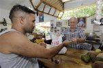 In this June 9, 2015, photo, shopper Miguel Ramirez, left, pays Angel Hernandez for his merchandise at a local fruit store in the Little Havana area of Miami.  The University of Michigan issues its monthly index of consumer sentiment for July on Friday, July 31, 2015. (AP Photo/Alan Diaz)
