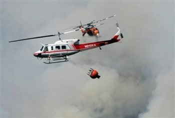 Two fire fighting helicopters pass near each other over Willow Creek Canyon as a wildfire continues burning in the Sierra near Bass Lake, Calif., Monday, July 27, 2015. More wildfires have torn across California so far this year compared with the same period of 2014, but firefighters said Monday that efforts to confine and extinguish the latest blazes have been more successful than in the past.  (Eric Paul Zamora/The Fresno Bee via AP)