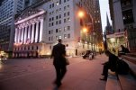 FILE - In this Oct. 8, 2014 file photo, a man walks to work on Wall Street, near the New York Stock Exchange, in New York. Global stocks were mixed on Friday, July 31, 2015, with China's stock market extending losses, after data showed the U.S. economy posted solid growth during the second quarter. (AP Photo/Mark Lennihan, File)