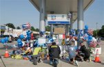 Mourners gather at a gas station in Houston on Saturday, Aug. 29, 2015 to pay their respects at a makeshift memorial for Harris County Sheriff's Deputy Darren Goforth who was shot and killed while filling his patrol car. On Saturday, prosecutors charged Shannon J. Miles with capital murder in the Friday shooting. (James Nielsen/Houston Chronicle via AP) MANDATORY CREDIT: JAMES NIELSEN/HOUSTON CHRONICLE