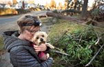 In this Nov. 20, 2015 photo, Shelly Aase embraces her dog Mattie Jo as they view damage in north Spokane, Wash., after storms left many without power. Aase is wearing a head lamp to see inside her house.  (Dan Pelle/The Spokesman-Review, via AP)