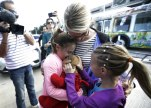 Courtney Gelinas, left, is hugged by her mother Kim Lariviere, center, after being reunited with her stuffed bear Rufus, at the Fort Lauderdale-Hollywood International Airport, Tuesday, Jan. 10, 2017. (AP Photo/Lynne Sladky)